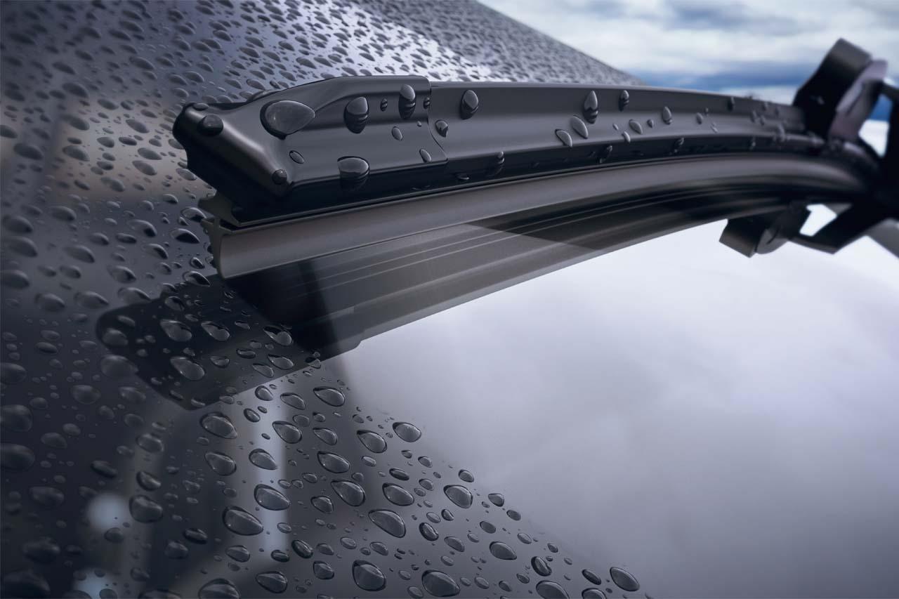 Imagem do para-brisa do carro com respingos de água e o limpador de para-brisa retirando dos respingos, ocasionados por um dia de chuva.